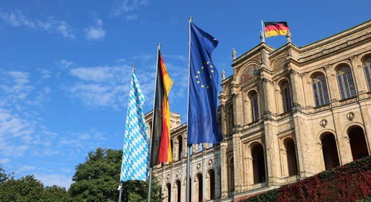 Maximilianeum in Bayern; davor drei Flaggen: Europa, Deutschland, Bayern.