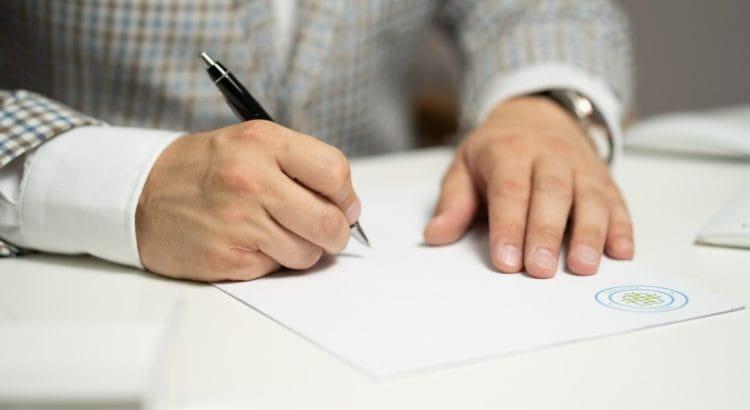 Mann im Anzug unterschreibt mit Kugelschreiber ein Dokument.