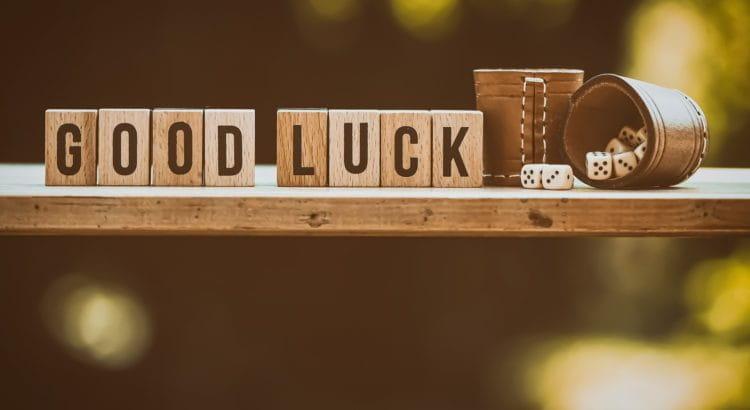 Würfel und Würfelbecher neben Steinen mit der Aufschrift Good Luck.