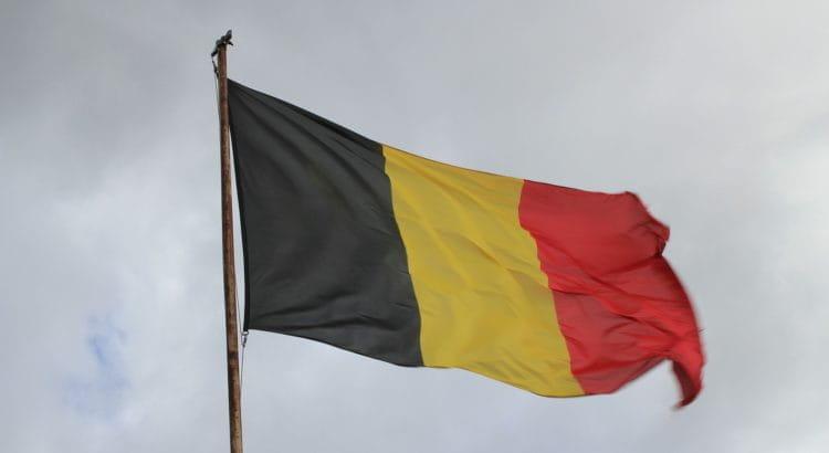 Belgische Nationalflagge wehend vor bewölktem Himmel.